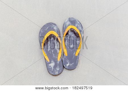 Brown flip-flops on sandy ocean beach summer and vacation concept.