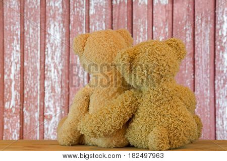 Back of a couple cute brown bears sitting on wood hugging each other with blurred red rustic wooden background
