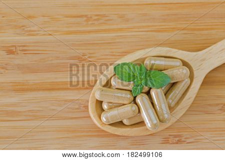 Wooden spoon full of herbal medicine in clear capsules, ideal for Homeopathic remedies on wood background with copyspace