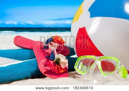 Summer vacation on the seaside. Mask goggles and color ball on a sand on beach background