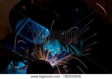 Flowing sparks, during welding work, abstract background of welder with sparks