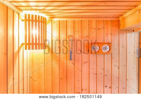 Bath thermometer hourglass and wooden interior of private sauna room.