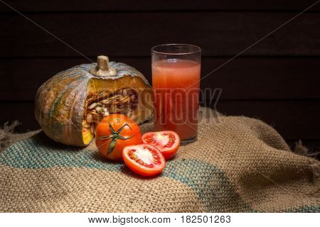 Tomato juice and Pumpkin with Red tomato Placed on a hemp sack
