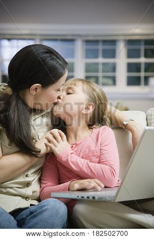 Hispanic mother kissing daughter with laptop
