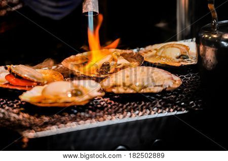 Delicious grilled scallop cooking on fire, street food in Tokyo