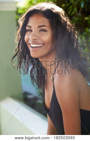 Young Latin American woman outdoors turns to camera smiling