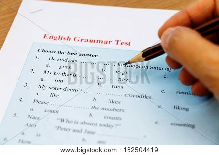 blue english grammar test with hand holding pencil on table