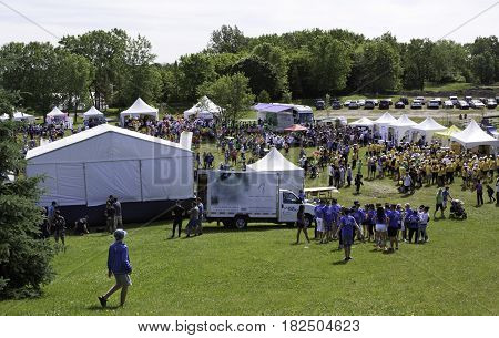 Laval, Quebec - June 14, 2015 - Landscape view of the large crowd of people in colorful t-shirts checking out the event tents attractions at the