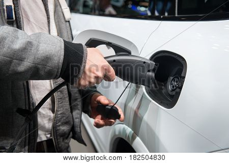 Man charging electro car. Man holding in hand power cable supply ready to plugged in into charging port.