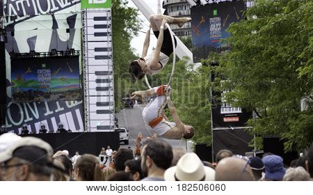 Montreal, Quebec - June 27, 2015 - Wide up view of two acrobatic street performers hanging from a suspended hoop as crowds of people watch at International Jazz Festival sign on a building in downtown Montreal, Quebec on a bright day at the end of June.