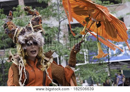 Montreal, Quebec - June 27, 2015 - Wide close up view of a woman street performer in a fancy costume and make-up at the International Jazz Festival in downtown Montreal, Quebec on a bright day at the end of June.
