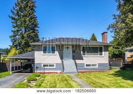 Modest residential house with car parked under the canopy on asphalt driveway. Family house with freshly mowed lawn on front yard