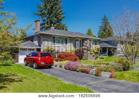 Modest residential house with red car parked on driveway in front. Family house with blossoming flowers on the front yard