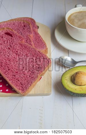 Pink whole wheat bread with espresso coffee and avocado on white woodle.