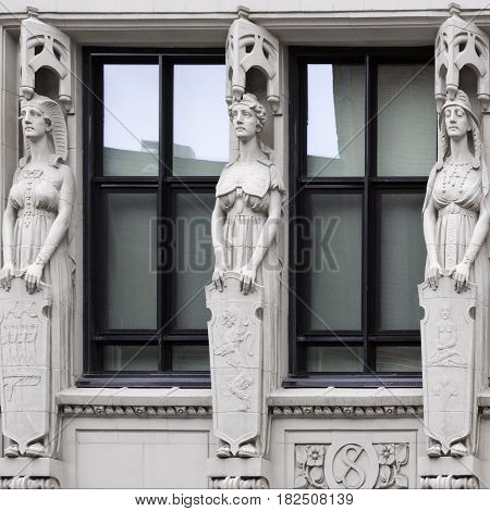 Montreal, Quebec - June 27, 2015 - Close up square view of three carved statues on a building in downtown Montreal, Quebec on a bright day at the end of June.