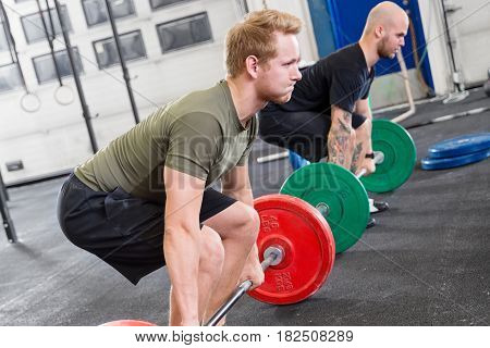 Two focused men taking deadlifts at fitness gym. Weight workout at the gym.