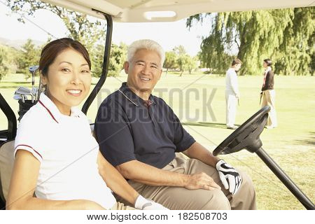 Senior Asian couple in golf cart