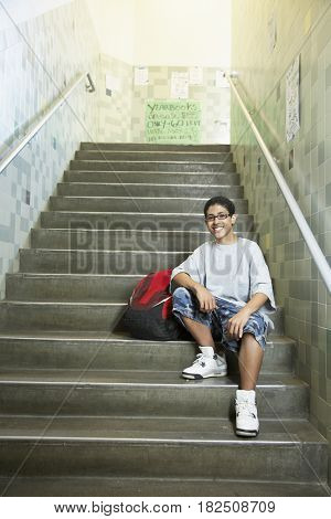 Teenaged boy sitting on school stairs indoors