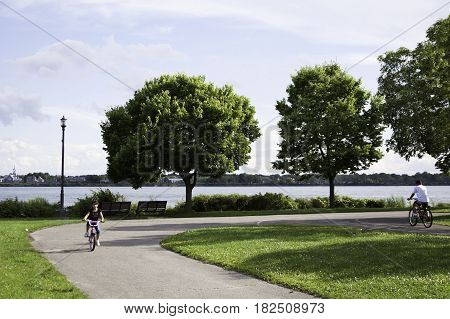Lachine, Quebec - August 1, 2015 -- Wide view of a little girl on a bicycle rounding a curve on the bike path in Rene Levesque Park with trees and the Lachine Canal in the background in Lachine, Quebec on a sunny day in August.