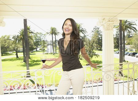 Hispanic woman leaning on balcony railing at resort