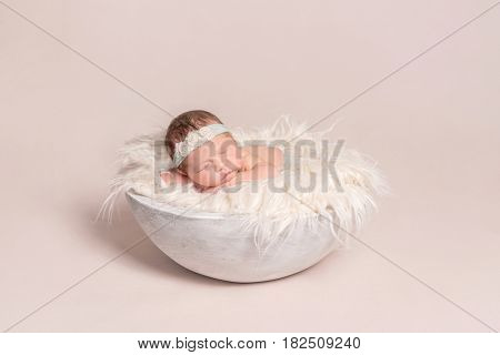 lovely baby girl napping on the huge soft pillow, wearing hairband decorated with flowers