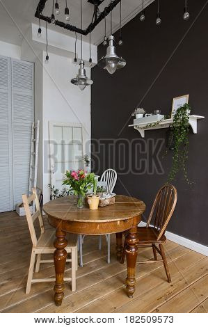 The interior of the dining room is furnished with a round wooden table, shelf, chairs.