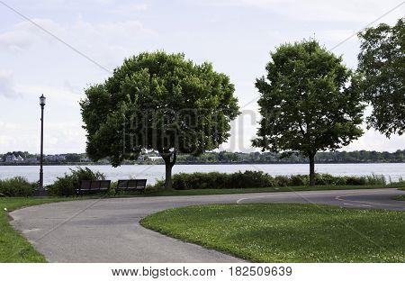 Wide view of the bike path as it curves in front of the trees and Lachine Canal in the background in Rene Levesque Park, Lachine, Quebec on a sunny day in August.