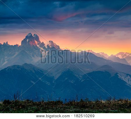 Dramatic morning view of mountain Ushba. Colorful autumn sunrise in the Caucasus mountains Upper Svaneti Georgia Europe. Artistic style post processed photo.