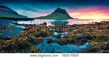 Colorful summer sunset with Kirkjufell mountain. Dramatic scene on Snaefellsnes peninsula with fall of tide in Atlantic ocean Iceland Europe.