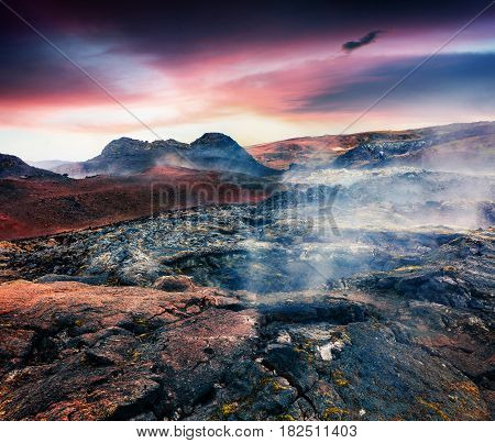 Fields of steamy waters in the Krafla volcano. Colorful exotic sunset with lava ground in the geothermal valley Leirhnjukur located near Lake Myvatn in north of Iceland Europe. Artistic style post processed photo.
