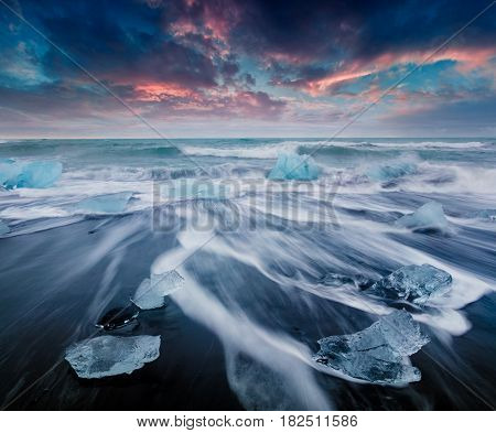 Blocks of ice washed by the waves on Jokulsarlon beach. Colorful summer sunrise in Vatnajokull National Park southeast Iceland Europe.Artistic style post processed photo.