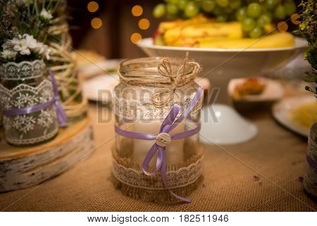 Designer jar decorated with ribbon and rope on the table . Handmade for the wedding.