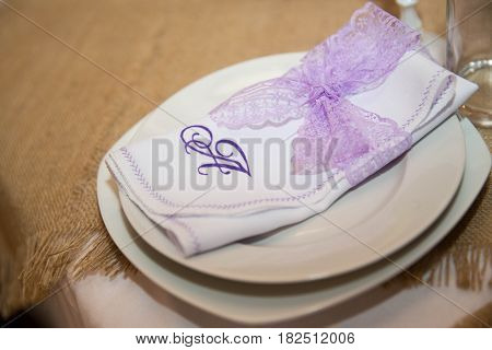 Napkin decorated with purple lace on the table for wedding celebrations. Handmade.
