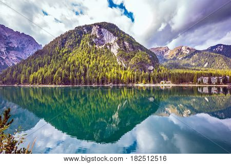 The concept of walking and eco-tourism. South Tyrol, lake Lago di Braies. Emerald expanse of water reflects the surrounding forest and mountains