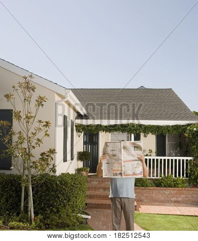 Man reading newspaper in front of house