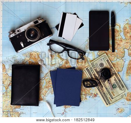 background - what to take for a trip. passport phone documents car keys map camera money sunglasses credit cards