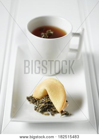 Close up of tea and fortune cookie on plate