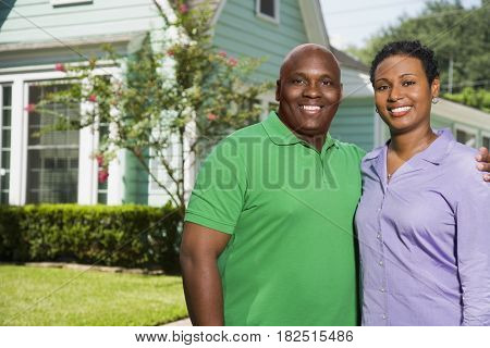 Portrait of African couple in front of house