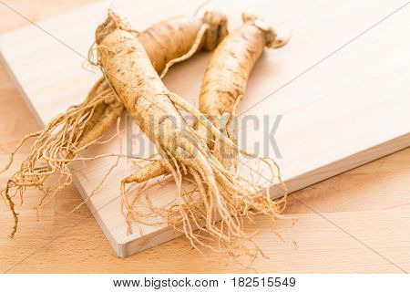 Fresh ginseng over wooden texture