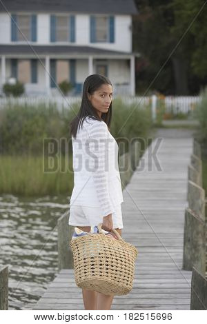 African woman walking on dock with beach bag