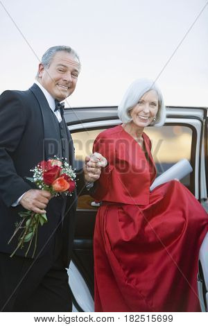 Well dressed senior couple with flowers getting into limousine