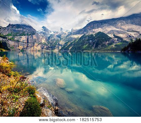 Colorful summer morning on unique lake - Oeschinen (Oeschinensee) UNESCO World Heritage Site. Beautiful outdoor scene in Bernese Oberland Alps Switzerland Europe.