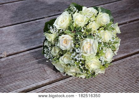 Bridal Bouquet with white Roses on wooden Plank