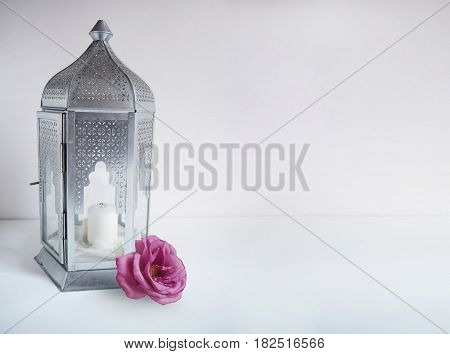 Ornamental silver Arabic lantern with rose flower on the table. Greeting card, invitation for Muslim community holy month Ramadan Kareem, festive background with a lot of empty space.