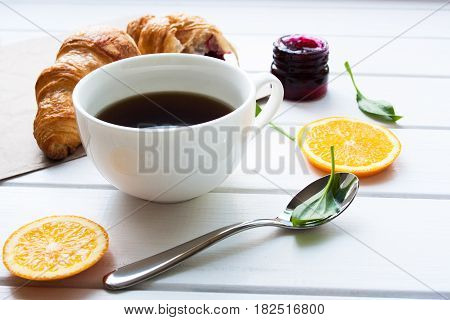 A cup of coffee with croissants on a white wooden table