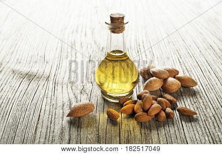 Almond oil in a glass bottle on a wooden background