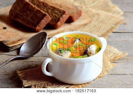 Easy fish soup recipe. Diet fish soup with potatoes, carrots and green onions in a bowl. Rye bread pieces, spoon on rustic wooden table. Closeup