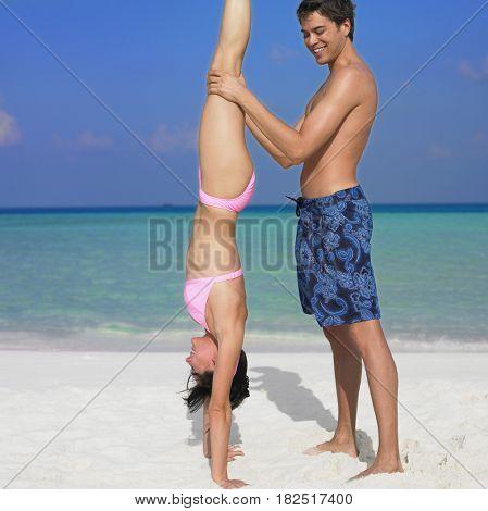 Man helping girlfriend do handstand at beach