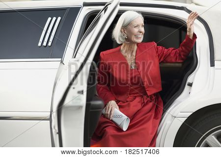 Well dressed senior woman waving from limousine