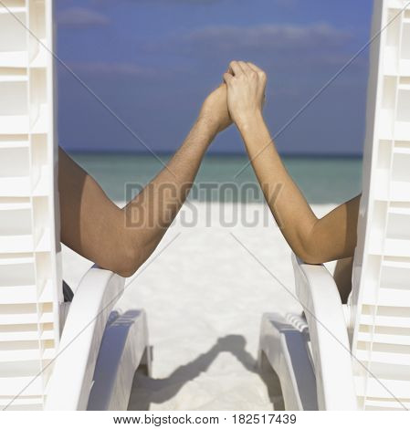 Couple holding hands in lounge chairs
